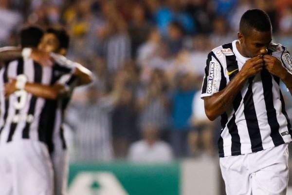 robinho-beija-o-escudo-do-santos-para-comemorar-o-primeiro-gol-dele-no-brasileirao-2014-1410657441753_1920x1080 (1050x591)